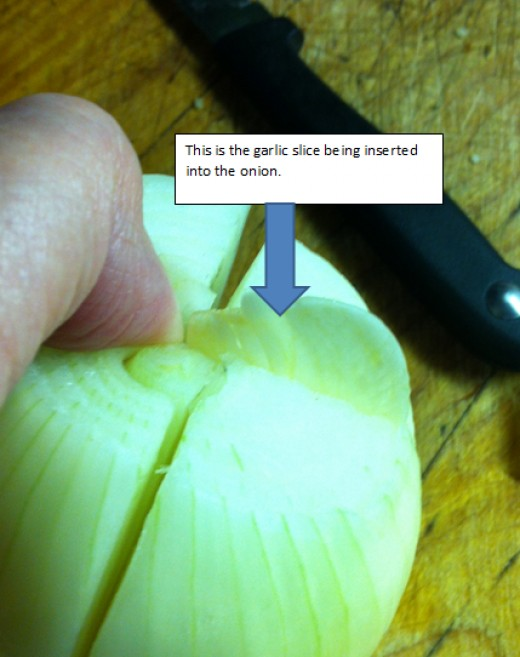 Garlic slice being inserted into onion.