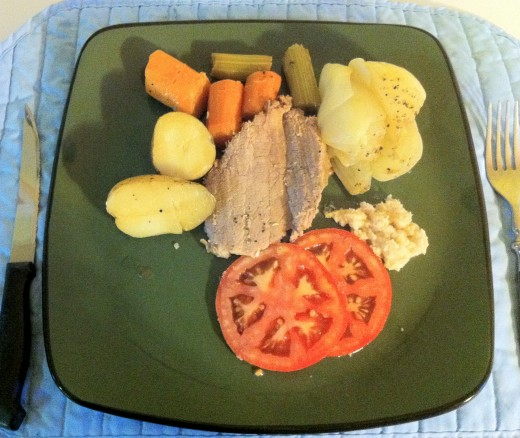 Dinner is served. Baked onions and beef pot roast served with tomato slices and horseradish sauce.