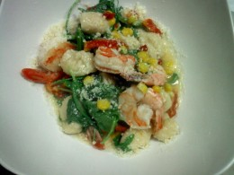 Shrimp gnocchi with corn, arugula and parmesean cheese in a white wine sauce