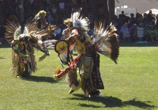 Men dancing in traditional regalia with eagle feather bustles, headdress and fans.
