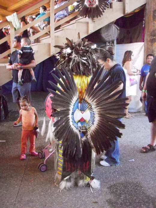 After the dance, young dancer finds his family.  His bustle and headdress are Eagle feathers.  In Canada, eagles are protected birds, and only First Nations people are allowed to possess them without heavy fines.