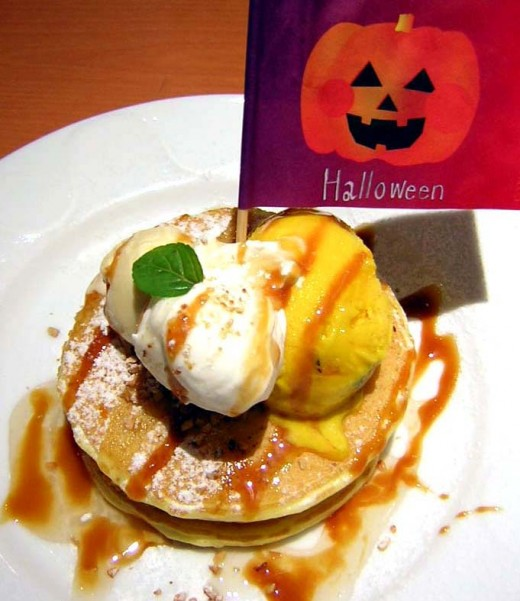 Denny's is famous for serving breakfast all day long.  The Grand Slam consists of two hotcakes, two eggs, two sausages and two strips of bacon.  This plate is being served on Halloween with a holiday flag.