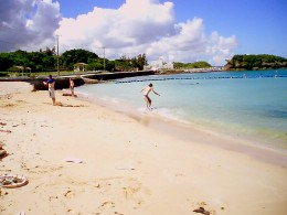 Skimboarding at the Kadena Marina with beach, volleyball net, and pavilions in  background