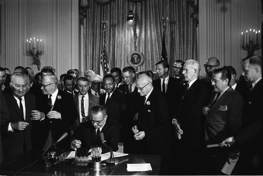Lyndon Johnson signs the Civil Rights Act in 1964 with Martin Luther King, Jr., among others looking on.