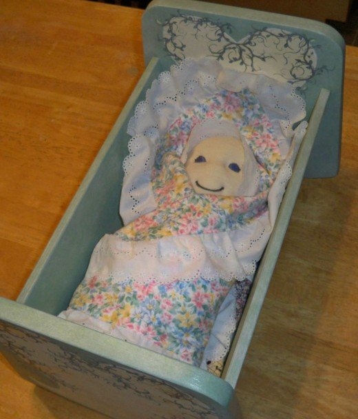 Yay, the baby in a blanket fits in the doll cradle just right, but her face still needs tweaking.  I can't send an alien in the cradle!