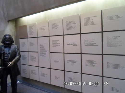 This is a statue of Frederick Douglas standing next to a wall of quotes he made during his lifetime.
