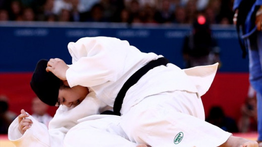 Wojdan Shaherkani, Saudi female judo competitor, adjusting her hijab while competing against Melissa Mojica of the US.