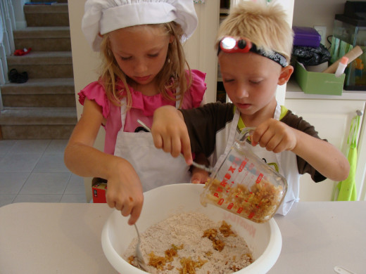 Together they add the apples to the dry ingredients.