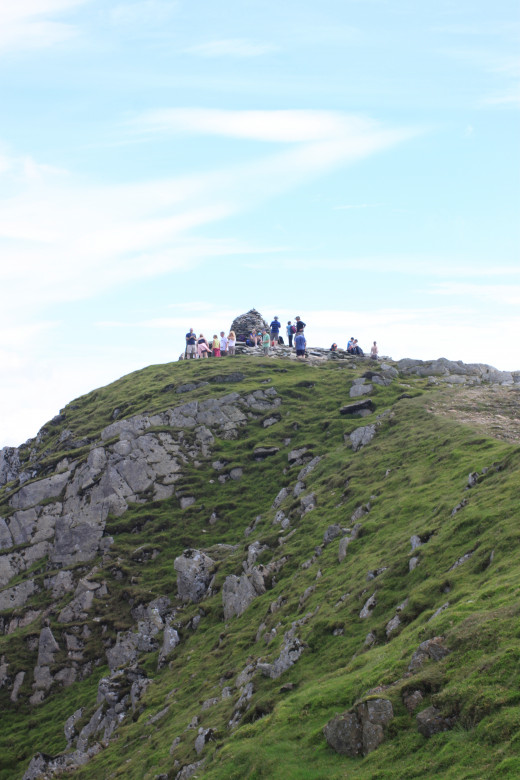 A group gathering at the summit of Coniston Old Man
