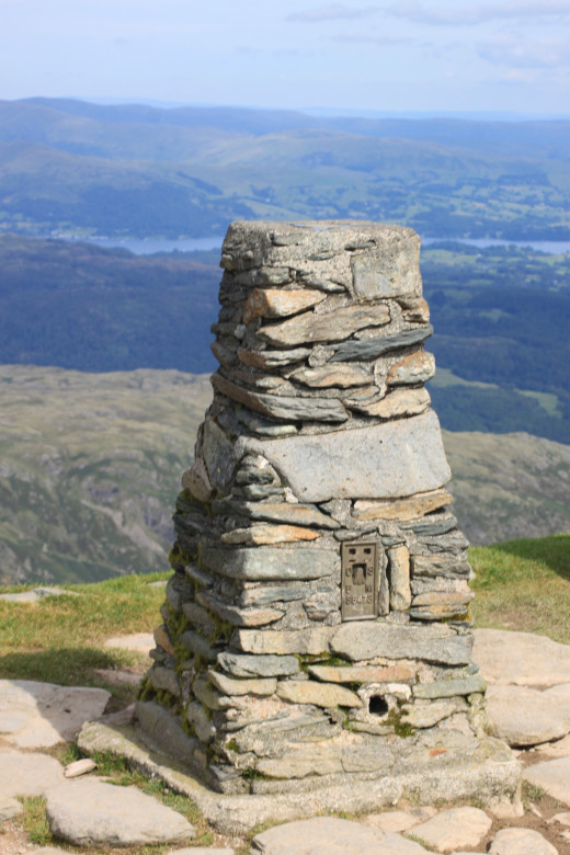 The trig point atop Consiton Old Man with Coniston Water in the distance