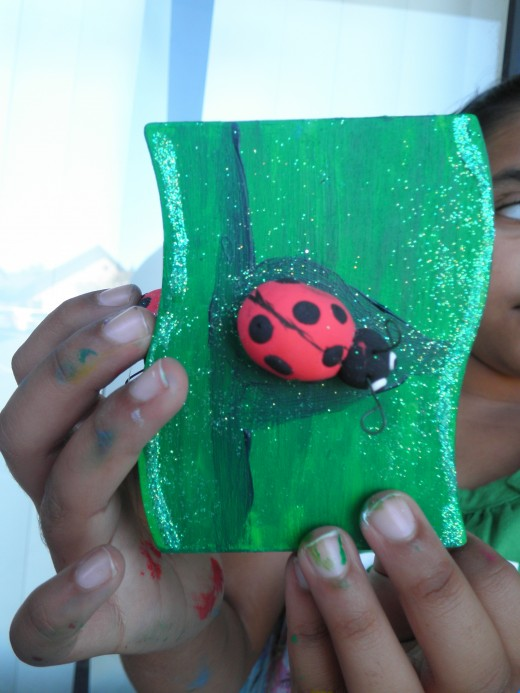A ladybug made out of Cloud Clay and hot-glued to an acrylic painted pencil box. What an awesome little keepsake! We also added some glitter to this project.