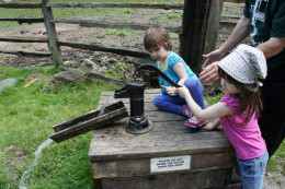 My daughters using a water pump as part of our study of pioneer life