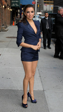 Eva Longoria in a short blue suit and high heels posing outside The Late Show
