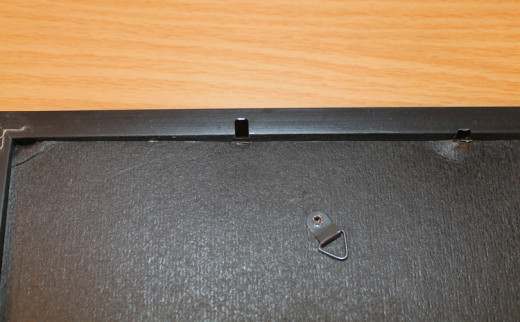Pry back or turn the metal tabs so you can remove the frame's back.