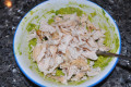 After the avocado has been mashed, shred the chicken into smaller pieces and mix together.