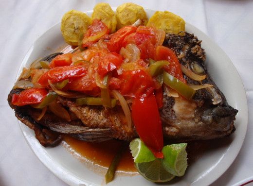 A grilled, deboned guapote, as served with onions, red sweet peppers and fried plaintains. It's not a particularly pretty fish, with a hump behind its head and a jaw full of teeth, but it tastes great.