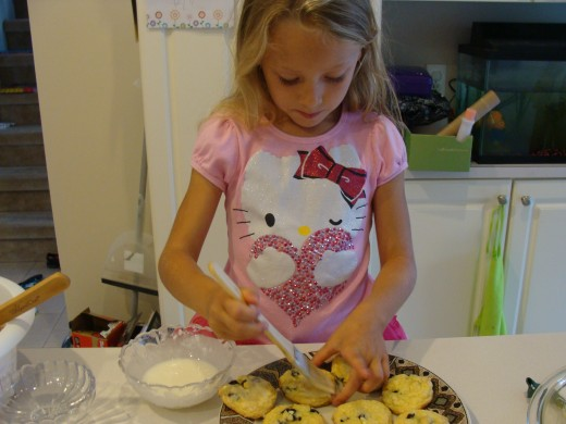 Grace carefully glazes each of the cooled lemon cookies.