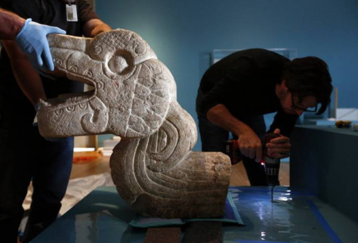 Staff installs sculpture in the form of a furthered serpent