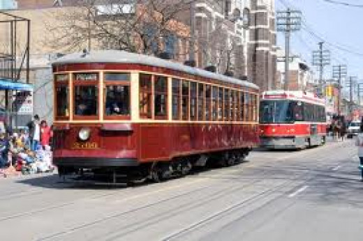The original streetcar from my young days in front, with the newer current example behind.  Streetcars are still running in Toronto today.