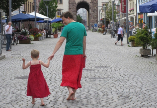 Father holding hands with his son in their small town as they wear a skirt and a dress