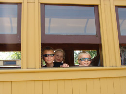 The kids peek their heads out of the train window.