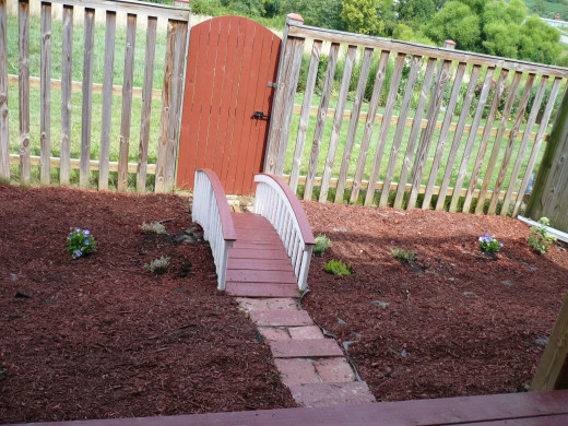 Painted gate and postcaps around the fence red. The stones steps were built to add ease for Marylou to walk the small hill in the yard.