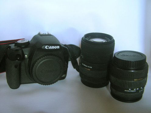 A DSLR camera body and two different lenses.
