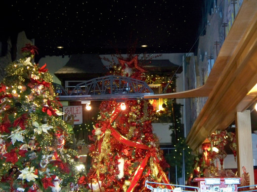 Train running overhead and through Christmas trees at the Incredible Christmas Place.