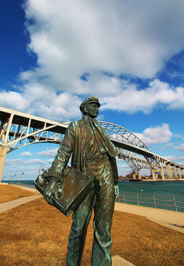 A statue of a young Thomas Edison in front of the Blue Water Bridge, Port Huron, Michigan.