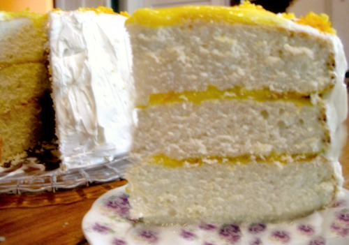 Yellow cake can have any number of frostings and fillings. In this image lemon curd fills between the layers while a Swiss buttercream covers the cake.