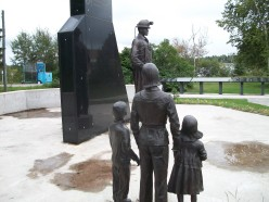 The Family sculpture, dwarfed by the larger-than-life statue of the Miner, at the Porcupine Miners' Memorial, Schumacher, Timmins