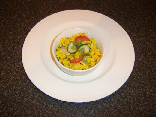 Rice is garnished with tomato, cucumber and coriander for service