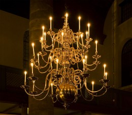 Antique chandelier lit up by candles in the Esnoga in Amsterdam