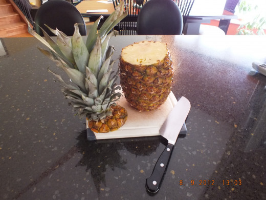 Wash your pineapple and start by cutting off the top. You can use the top to make a cool display for your pineapple. We do eat with our eyes.