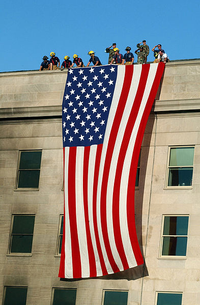 Soldiers from the 3rd Infantry render honors as fire fighters and rescue workers unfurl a huge American flag over the side of the Pentagon as rescue and recovery efforts continued following the September 11, 2001 terrorist attack.