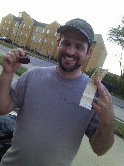 Keep your eyes and mind open when geocaching. This one was stuck (magnetized) to the underside of a sewer drain! - A micro, traditional cache. In his left hand is a log, which was located within the cache.