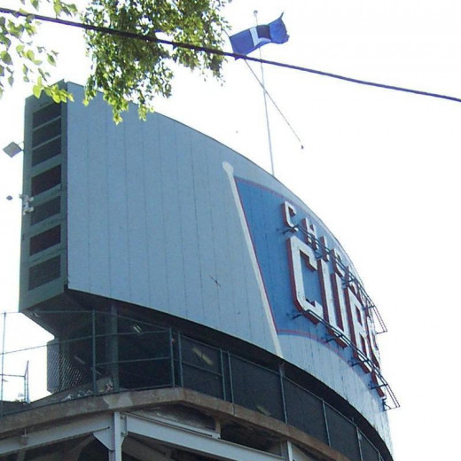 "The ""L"" flag, signalling to CTA El riders that the Cubs lost that day, flies over the iconic center field scoreboard."