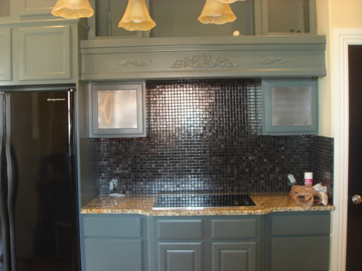 Small, shiny black tiles coordinate with the black appliances.