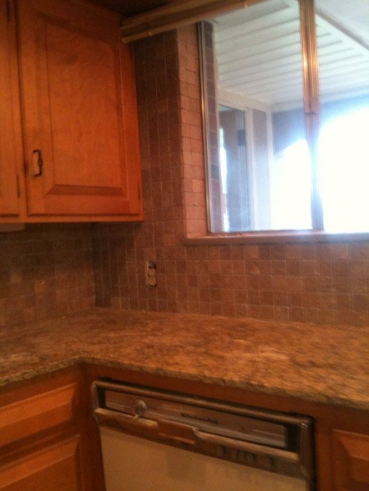 Rather than introducing an additional color to this kitchen, the tiles were installed surrounding the whole window.