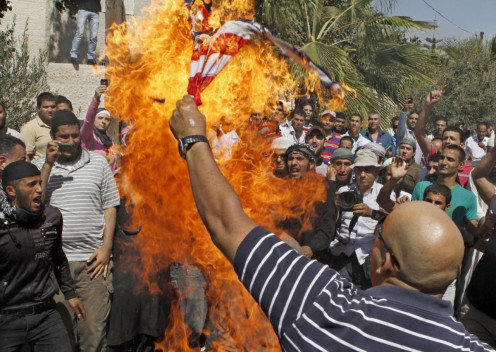 Photo shows an Islamist Jordanian protester burning the U.S. flag near the U.S. embassy in Amman, Jordan, Friday, Sept. 14, 2012, as part of widespread anger across the Musl im world about a film ridiculing Islam's Prophet Muhammad.