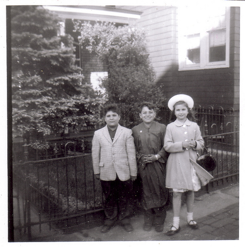 Three kids in their traditional church frocks, circa 1960's