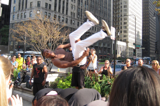 Street performers jump and flip on the sidewalk for passersby.