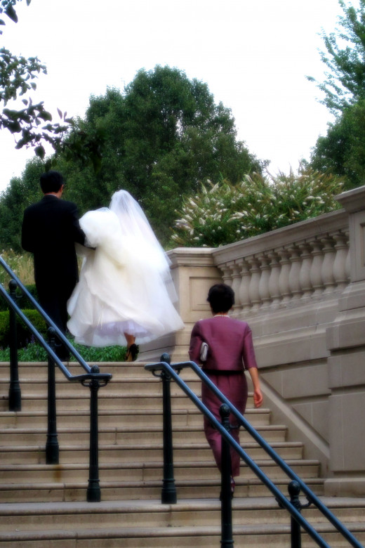 A wedding couple running up the stairs with an older female trailing behind them.