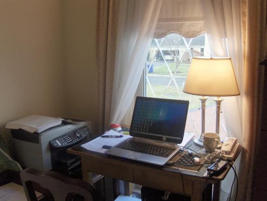 A small desk area in front of a window that has diamond bevels in the window to give reflective privacy but a great outlook on the world while you are on the computer doing your work.