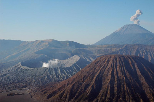 Batok,(foreground), Bromo (with smoking crater in the middle), and Semeru (with smokes in the background) seen from Mt. Pananjakan.