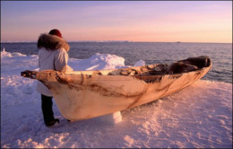 An Inupiat person preparing to launch a boat in an area that typically would have been frozen in that time of year.