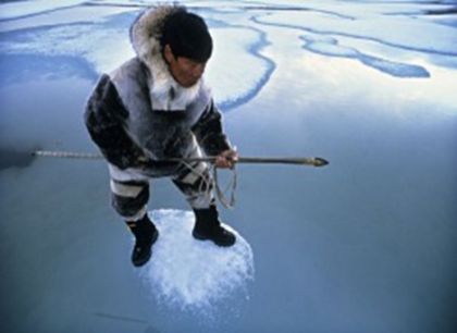 An Inupiat fisherman as he tests the thin ice in preparation for his traditional mode of subsistence.