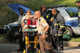 An injured police officer is taken to an ambulance after being injured in a crash. Photo was taken from the median strip with a telephoto lens