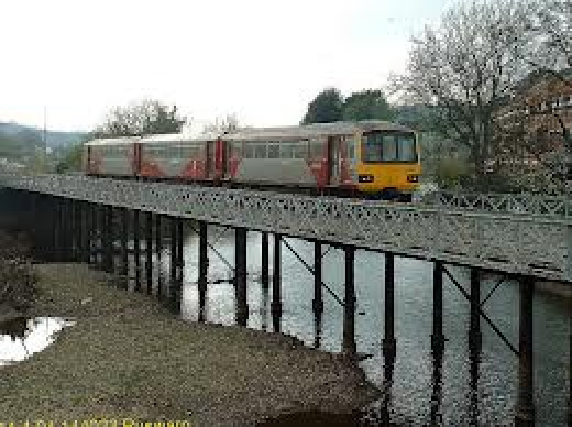 Pacer train for Whitby trundles over Ruswarp's twin trestle bridge. Only one side is in use and there's a footbridge on one side.