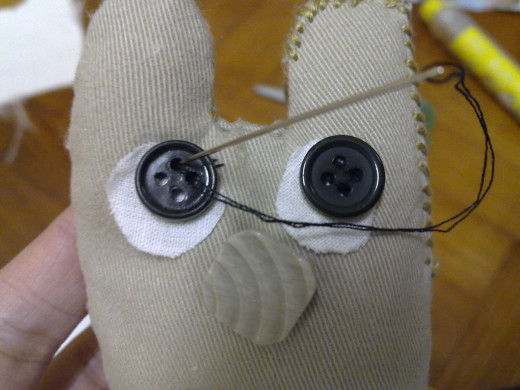 Sew a pair of black buttons on top of the white eyes